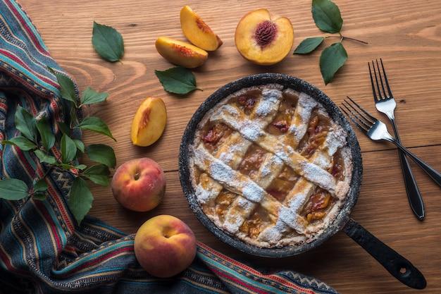 Perziktaart in een gietijzeren koekenpan ligt op een houten tafel.