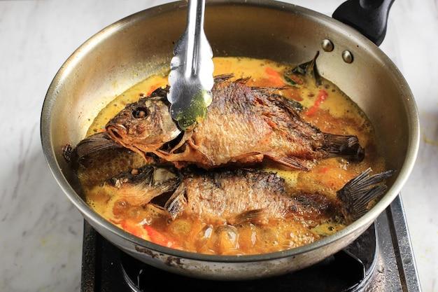 Pesmol-vis koken met goudvis. voeg gebakken vis toe aan de pan. pesmol typisch visrecept uit west-java, indonesië, met zoetzure en pittige smaak