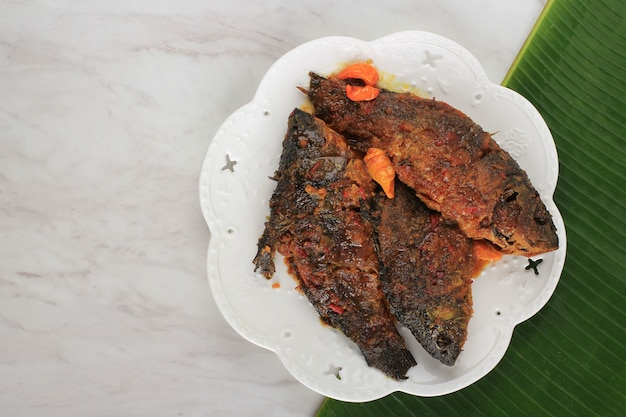 Pesmol vis met goudvis. voeg gebakken vis toe aan de pan. pesmol typisch visrecept uit west-java, indonesië, met zoetzure en pittige smaak
