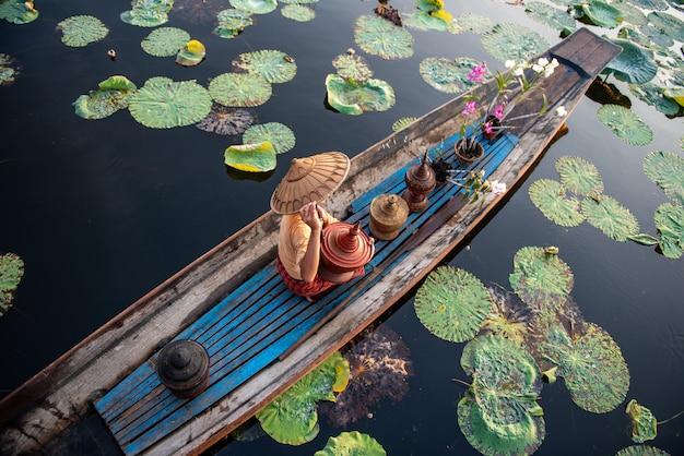 Peson neemt een boot van een sloppenwijk aan de oever van de rivier de irrawaddy naar de stad