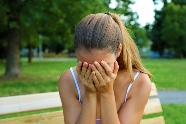 Pesten, discriminatie of stressconcept. trieste tiener die alleen in het park huilt. boos jonge vrouwelijke student met angst.