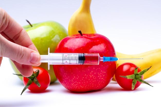 Pesticiden en nitraten worden met een spuit in groenten en fruit geïnjecteerd. ggo-concept en genetisch gemodificeerd organisme. gmo-vrije en natuurlijke gezonde producten zonder chemische additieven.