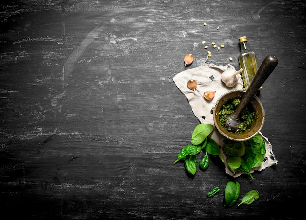 Pesto in een vijzel met knoflook en olijfolie. op de zwarte houten tafel.