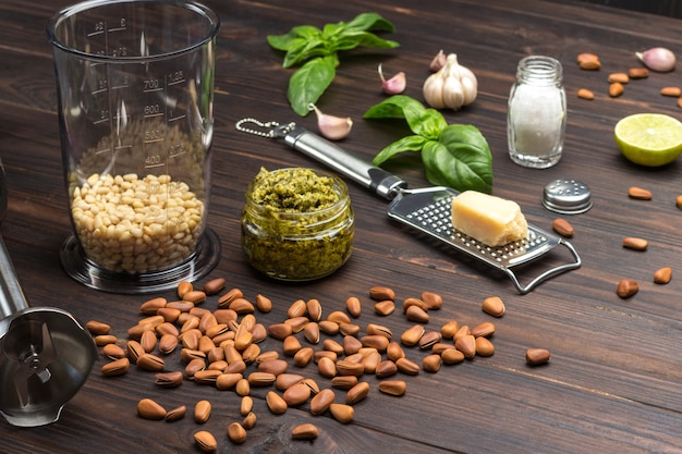 Pesto. ongeschilde pijnboompitten, pestosaus in pot, parmezaanse kaas op rasp, knoflook, basilicum, blenderkan, garde, citroen. bovenaanzicht. donkere houten achtergrond