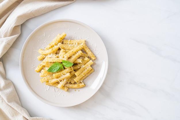 Pesto rigatoni pasta met parmezaanse kaas - italiaans eten en vegetarische eetstijl