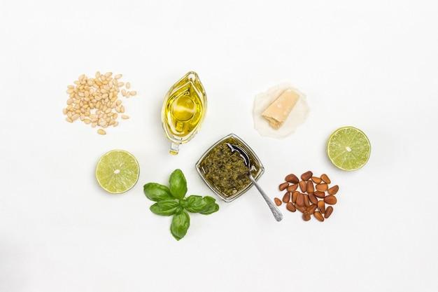 Pesto saus. pijnboompitten. parmezaanse kaas op papier. pesto in kom, basilicumblaadjes, knoflook en citroen.