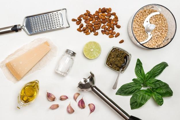 Pesto saus. snijder met pijnboompitten, garde, rasp, pestokom, basilicumblaadjes, parmezaan, knoflook, citroen. plat leggen. witte achtergrond