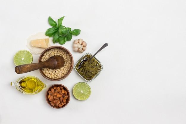 Pestosaus en ingrediënten. pijnboompitten in houten vijzel, ongeschilde pijnboompitten in kom, olijfolie, pestokom, basilicumblaadjes, parmezaan, knoflook, citroen. plat leggen. witte achtergrond. kopieer ruimte