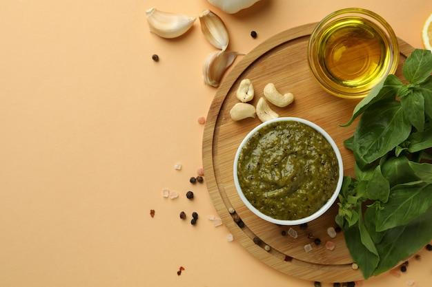 Pestosaus en ingrediënten voor het koken op beige achtergrond