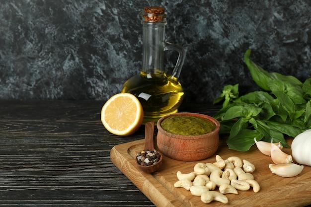Pestosaus en ingrediënten voor het koken op houten achtergrond