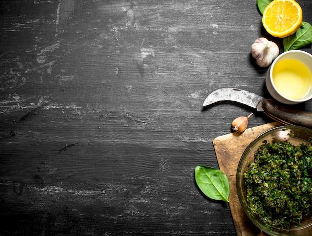 Pestosaus met olijfolie, knoflook en andere ingrediënten op de zwarte houten tafel.