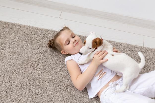 Pet jeugd en dier concept portret van klein kind meisje liggend op de vloer met puppy jack