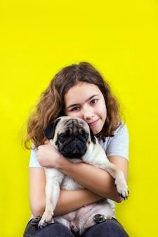 Pet liefde. het krullende tienermeisje koestert haar droevige pug hond met liefde