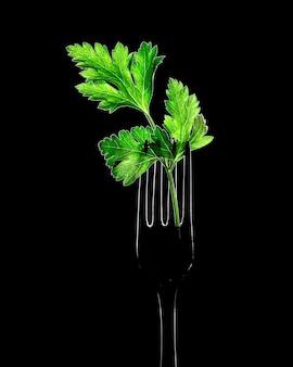 Peterselieblaadjes op een vork op een zwarte achtergrond