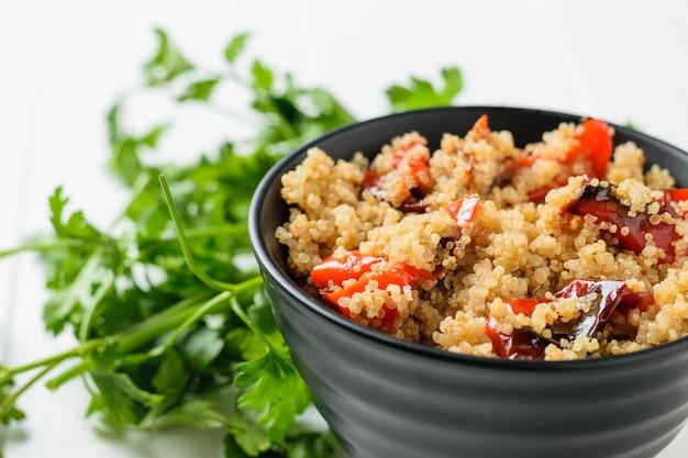 Peterseliegroenten met een kom quinoasalade en gebakken groenten. vegetarisch gerecht.