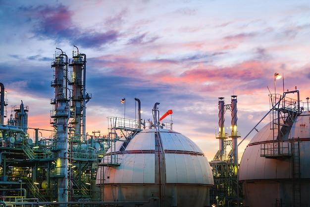 Petrochemische fabriek op zonsonderganghemel met boltanks voor gasopslag, industriële productie van aardolie, apparatuur voor gas- en olieraffinaderijen