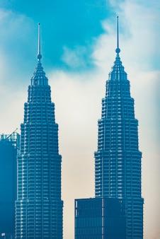 Petronas twin towers (liefkozend als klcc) en de omliggende gebouwen tijdens zonsondergang gezien vanuit de skybar