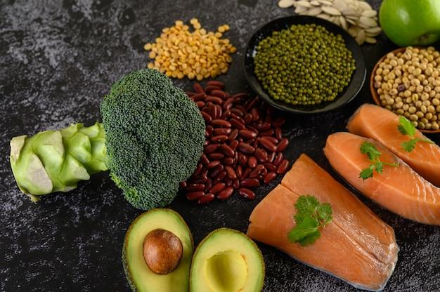 Peulvruchten, broccoli, fruit en zalm op een zwarte cementvloer.