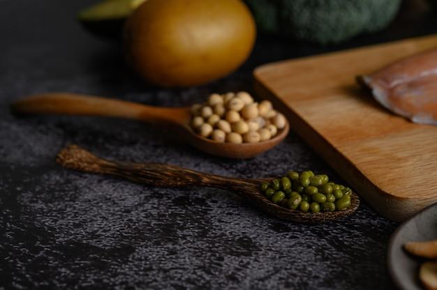Peulvruchten, stukjes zalm en kiwi op een zwart cement vloeroppervlak.