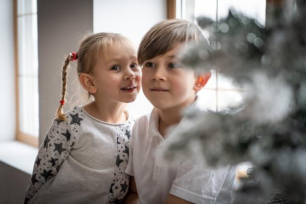 Peuter broers en zussen kinderen zitten in het raam, kijken naar de nachtelijke hemel santa vrolijk kerstfeest gelukkig nieuwjaar