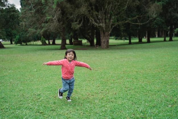 Peuter die in het park loopt en haar hand uitspreidt