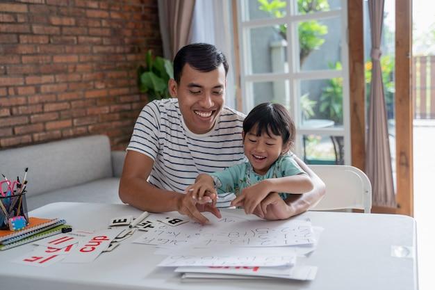 Peuter die met haar vader thuis bestudeert