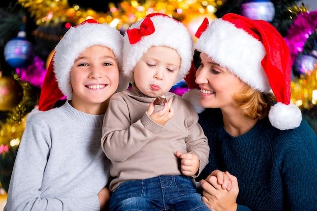 Peuter eet het zoete snoepje in een kring van familie. glimlachende jonge moeder met twee zonen in kerstmanhoeden.