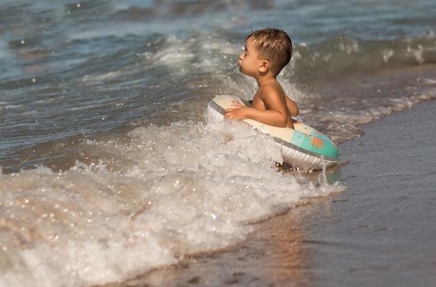 Peuter europese jongen zit in de zee