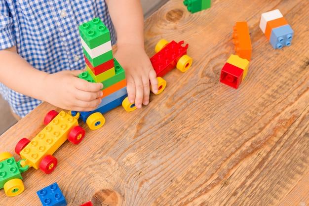 Peuter heeft plezier en bouwt uit heldere kleurrijke plastic bouwstenen op houten tafel