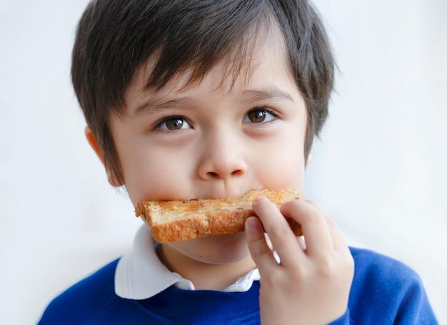 Peuter jongen die honing eet die op zijn ontbijt wordt geroosterd