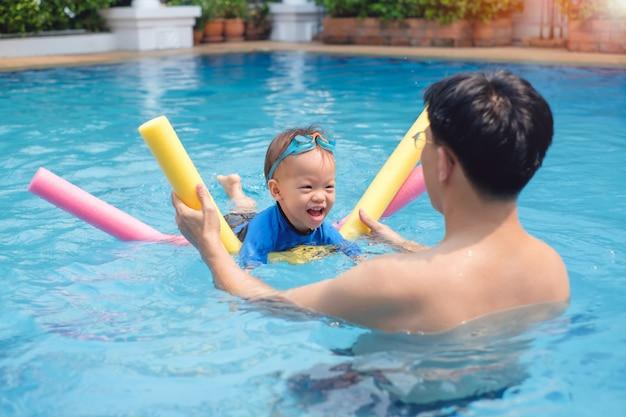 Peuter jongen kind zwembril leren leren zwemmen met zwembad noodle bij buitenzwembad
