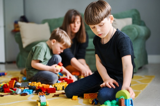Peuter jongen spelen met bouwblokken thuis moeder en broer op de achtergrond