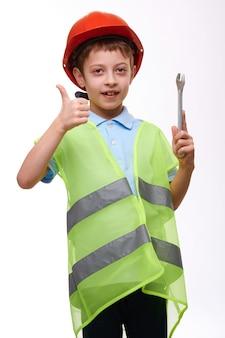 Peuter kind bouw vest in oranje helm bedrijf moersleutel en duim omhoog gebaren op witte geïsoleerde achtergrond