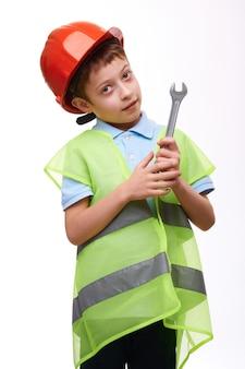 Peuter kind bouwvakker in de oranje moersleutel van de helmholding op wit geïsoleerde achtergrond