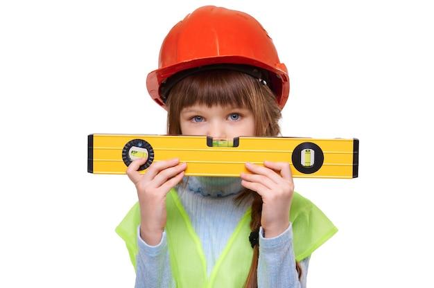 Peuter kind meisje bouw vest dragen en helm bouwen houdt niveau op witte geïsoleerde achtergrond