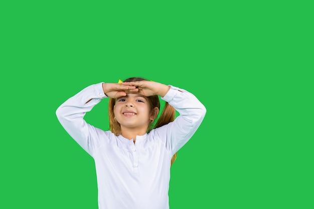 Peuter meisje met een glimlach kijkt in de verte met beide handen op het voorhoofd