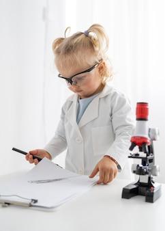 Peuter met veiligheidsbril en microscoop