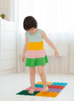 Peuter op baby voetmassagemat. oefeningen voor benen op orthopedisch massagetapijt. preventie van platvoeten en hallux valgus