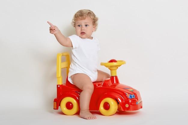 Peuter poseren zittend op speelgoed raceauto, wegkijken en aangeven met wijsvinger, jurken witte romper, babyjongen binnen spelen