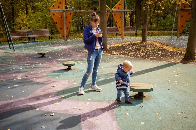 Peuter rent door het park moeder kijkt naar de telefoon kind op de speelplaats onbeheerd gevaar