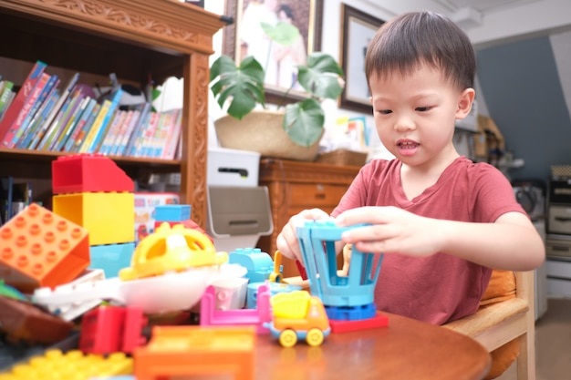 Peuter spelen met speelgoed, schattige kleine aziatische peuter jongen kind plezier spelen met kleurrijke plastic blokken binnen thuis