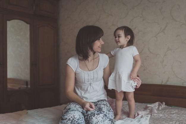 Peuterdochter die jonge donkerharige moederlevensstijl, pastelkleuren kammen,