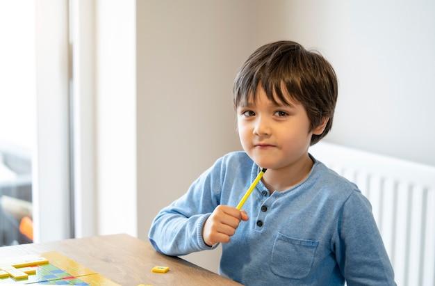 Peuterjong geitje die engels woordenspel leren, kindjongen concentreerde zich thuis met spellings engelse brief met ouder. afstandsonderwijs, activiteit voor kinderen voor thuisonderwijs tijdens zelfisolatie