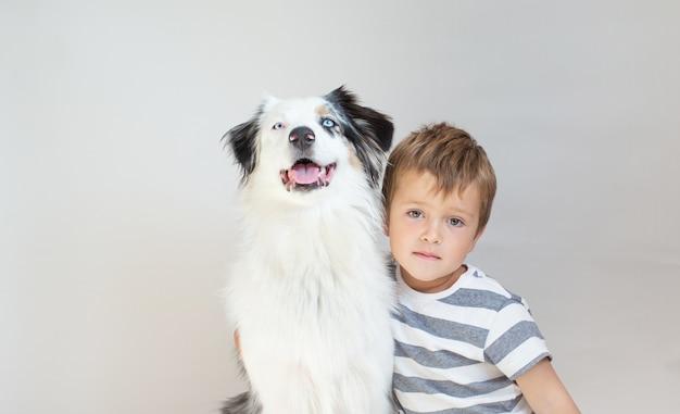Peuterjongen die australische herderhond binnen omhelst