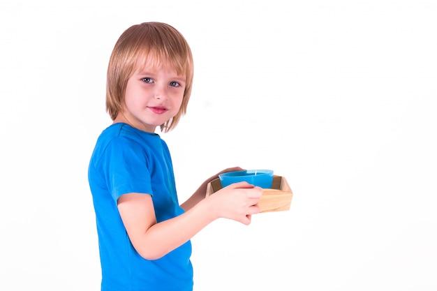 Peuterjongen die zich met een dienblad van montessori-materialen voor een les van het praktische leven op een witte achtergrond bevindt,