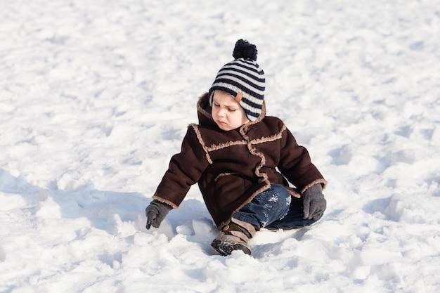 Peuterjongen loopt op de besneeuwde grond
