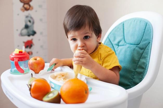 Peuterjongen met donker haar in een geel t-shirt zit op een kinderstoel en dineert op fruit.