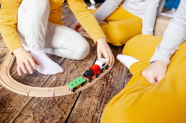 Peuterjongens bouwen spoorweg en spelen met houten trein zittend op de vloer in de woonkamer. kleine jongens spelen met een speelgoedauto. kinderen spelen. zachte focus
