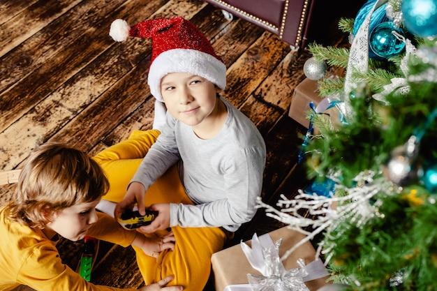 Peuterjongens bouwen spoorweg en spelen met speelgoedtrein onder de kerstboom. kinderen met kerstcadeaus. kersttijd.