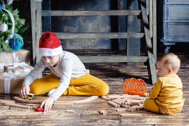 Peuterjongens met kerstmuts bouwen spoorweg en spelen met speelgoedtrein onder de kerstboom. ingericht huis voor wintervakanties. kinderen met kerstcadeaus. kersttijd.